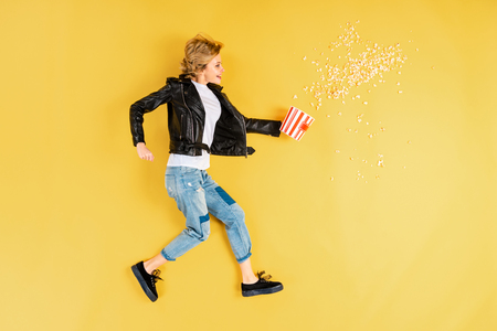 Short-haired woman in leather jacket holding popcorn on yellow background Stock Photo