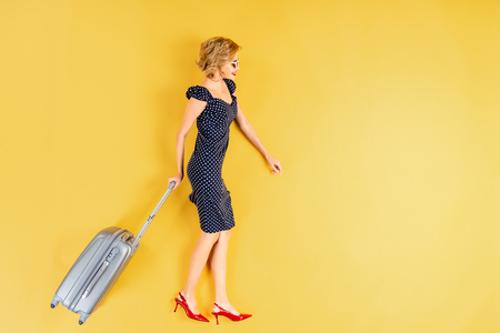 Woman in dress and high-heeled shoes holding suitcase on yellow background