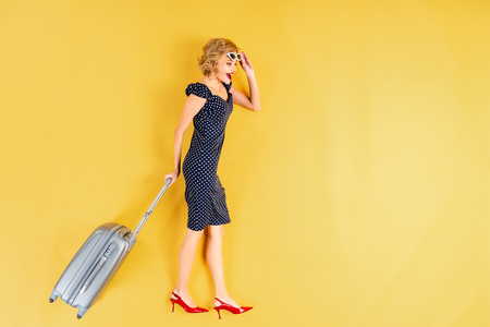 Charming young woman in dress and high-heeled shoes holding suitcase on yellow background