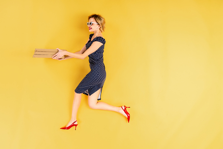 Full length view of woman in black dress holding pizza on yellow background