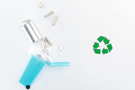 Batteries, can and paper falling down into toy trashcan on grey background with recycling symbol Stock Photo