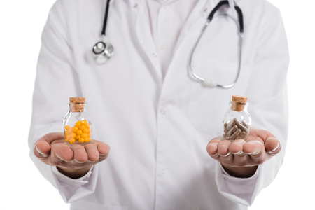 cropped view of male doctor holding two bottles with pills isolated on white Stock Photo