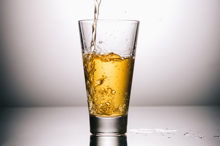 glass of tea and splashes on grey background with copy space Stock Photo - 117867909