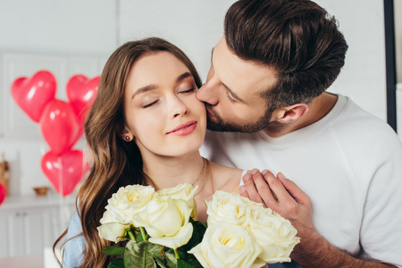 selective focus of happy girl holding roses bouquet with closed eyes while boyfriend kissing cheek and embracing girlfriend