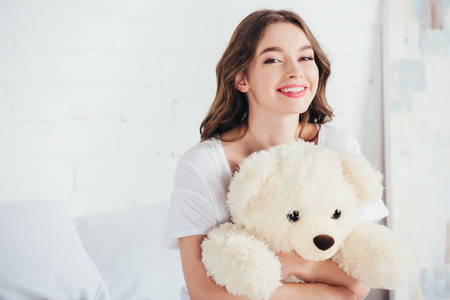 selective focus of happy woman smiling and hugging teddy bear in bed