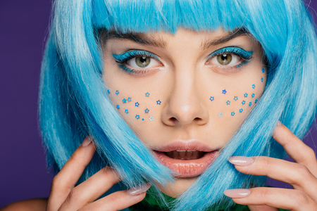 glamor girl with blue wig, makeup and stars on face, isolated on purple