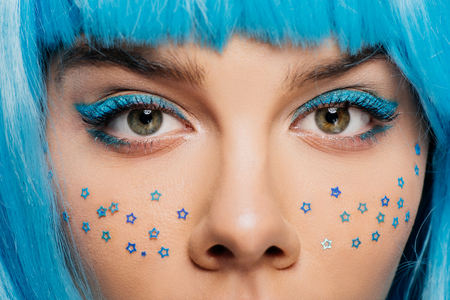 close up of fashionable girl with blue wig, makeup and stars on face, isolated on purple