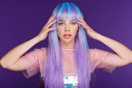 pretty girl posing in violet wig with stars on face, isolated on purple