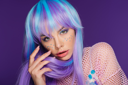 fashionable girl posing in violet wig with stars on face, isolated on purple Banco de Imagens