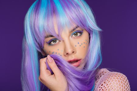 fashionable young woman posing in violet wig with stars on face, isolated on purple