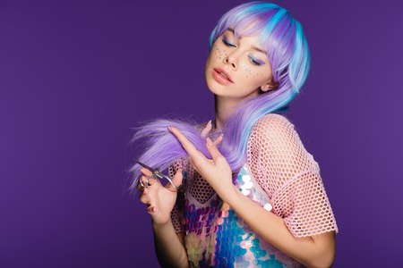 fashionable girl with stars on face cutting violet hair with scissors, isolated on purple Фото со стока - 117867478