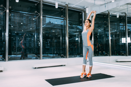 slim asian sportswoman standing on fitness mat and stretching at modern gym
