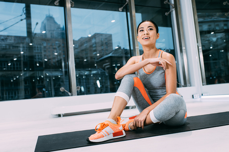 attractive asian sportswoman sitting on mat and smiling at gym Foto de archivo - 117877936
