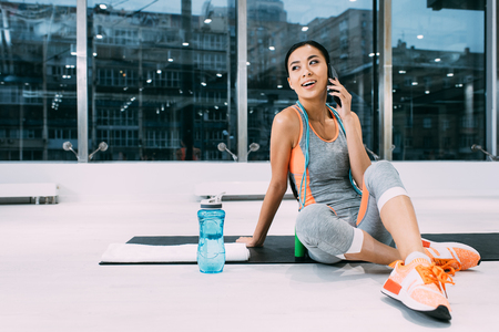 attractive asian sportswoman sitting on fitness mat and talking on smartphone in sports center