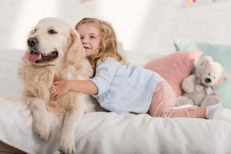 adorable kid hugging golden retriever dog on bed in children room
