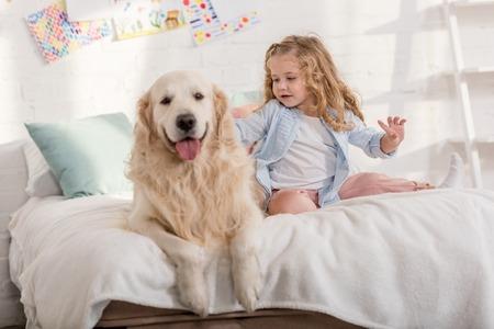 adorable kid palming golden retriever on bed together in children room