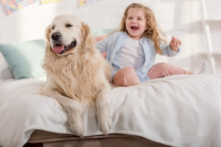 laughing adorable kid and cute golden retriever sitting on bed together in children room