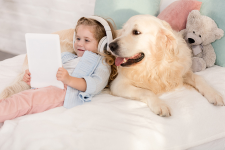 adorable child listening music with tablet and leaning on cute golden retriever on bed in children room