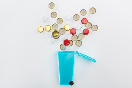 Top view of bottle caps falling down into blue toy trashcan on grey background