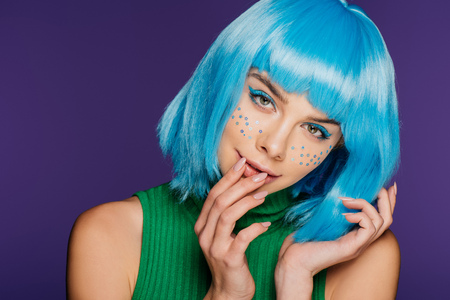 attractive fashionable girl with blue wig and stars on face, isolated on purple
