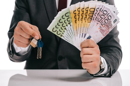 cropped view of businessman holding keys and euro banknotes isolated on white, mortgage concept Stock Photo
