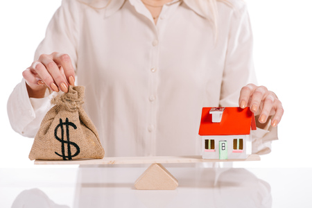 cropped view of businesswoman weighing house model and moneybag isolated on white, mortgage concept