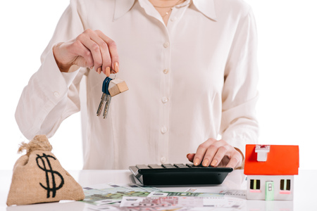 cropped view of businesswoman holding keys and using calculator isolated on white, mortgage concept Stock Photo
