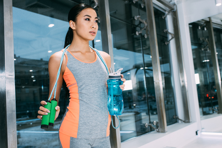 beautiful asian sportswoman holding sports bottle with water and skipping rope at gym Reklamní fotografie