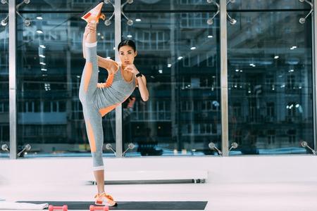 atletisch Aziatisch meisje in sportkleding met been omhoog op fitnessmat in de sportschool
