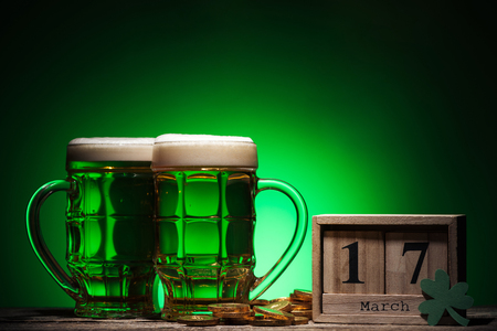 glasses of green irish beer near golden coins and cube calendar on green background