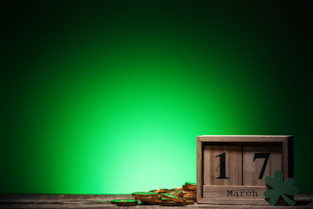 golden coins near cube calendar with date on green background Stok Fotoğraf