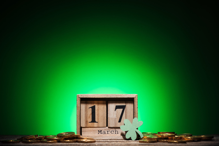 cube calendar with date near golden coins and shamrock on green background Stock Photo