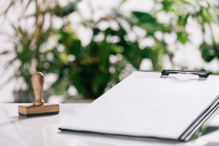 selective focus of stamp and clipboard on white desk, mortgage concept
