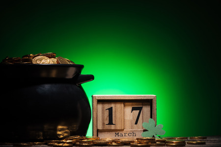 cube calendar with date near golden coins in pot on green background Stock Photo