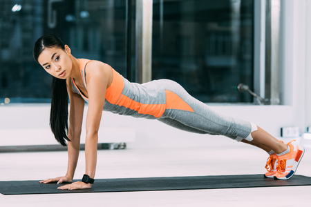 slim asian girl doing press ups on fitness mat at gym