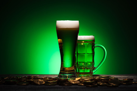glasses of irish beer standing near golden coins on wooden table on green background Stok Fotoğraf