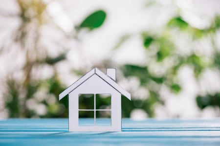 selective focus of paper house on blue wooden desk, mortgage concept Stock Photo