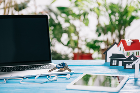 selective focus of digital tablet, laptop with blank screen and keys near headphones and house model on wooden desk, mortgage concept