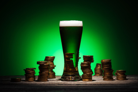 glass of ale standing on wooden table near golden coins on green background Stok Fotoğraf