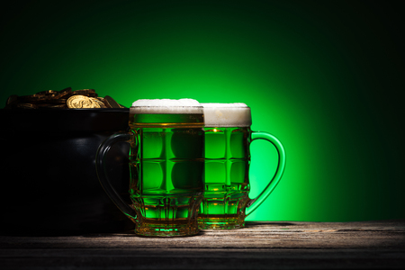 glasses of ale near pot with gold on st patricks day on green background