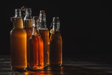 homemade organic tea in glass bottles isolated on black Banco de Imagens