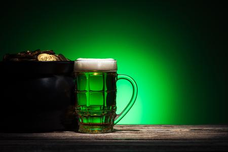 glass of ale near pot with gold on st patricks day on green background Stok Fotoğraf - 117908477