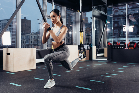 athletic asian girl stretching with resistance bands in fitness center