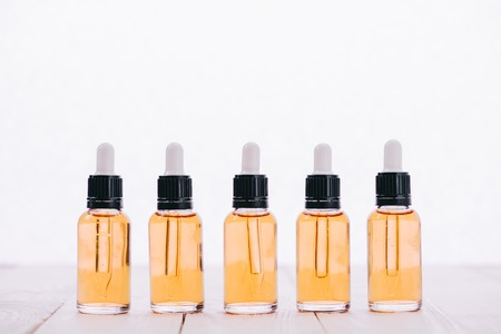 row of cbd oil in bottles with droppers on wooden surface isolated on white
