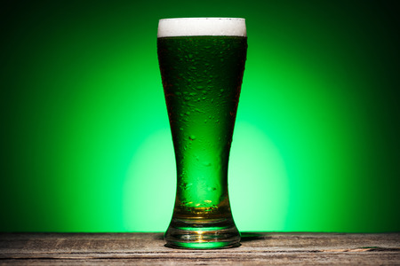 glass of green irish ale standing on wooden table on green background