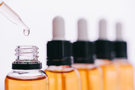 Focus sélectif de goutte d'huile de cannabidiol avec compte-gouttes isolated on white