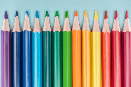 top view of rainbow multicolored pencils arranged in horizontal line on blue background, lgbt concept