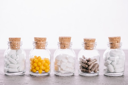 row of bottles with corks and different pills isolated on white Stock Photo - 117908646