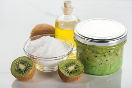 selective focus of glass container with kiwi puree, bowl of salt, oil bottle and kiwi on white surface 스톡 콘텐츠
