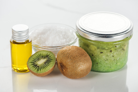 selective focus of glass containers with kiwi puree and oil, bowl of salt, and kiwi on white surface